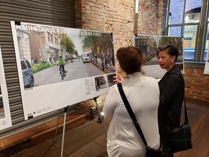Photo of two people viewing a display board showing design options for Pioneer Square in a large hall filled with other people attending an open house.