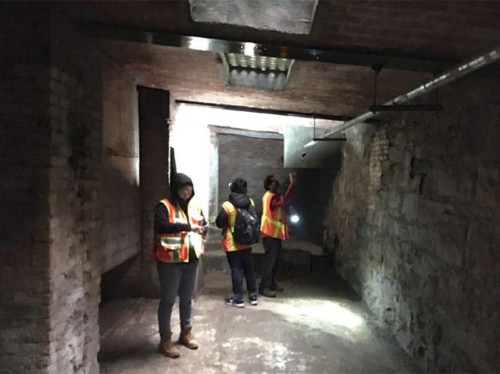 Three people in construction vests investigate inside an areaway, a large open space beneath a sidewalk