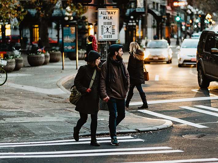 : Photo of two people crossing a street on foot on a fall afternoon in Pioneer Square
